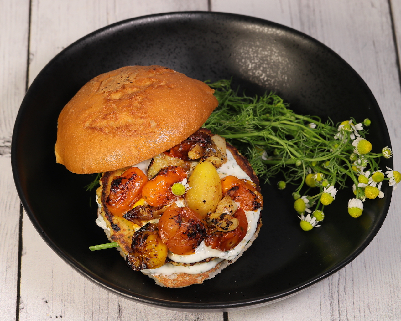 Salmon Burger with dill and chamomile yogurt, spinach and roasted tomatoes Phood Farmacy